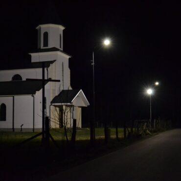 Iluminowany kosciół z wieżą i białą elewacją. Przed kościołem dwie świecące latarnie uliczne