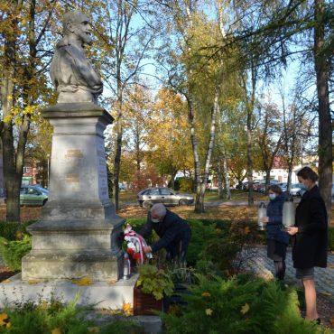 Mężczyzna składa wieniec pod popiersiem na postumencie. Obok stoja dwie kobiety i trzymaja szkalne lampiony