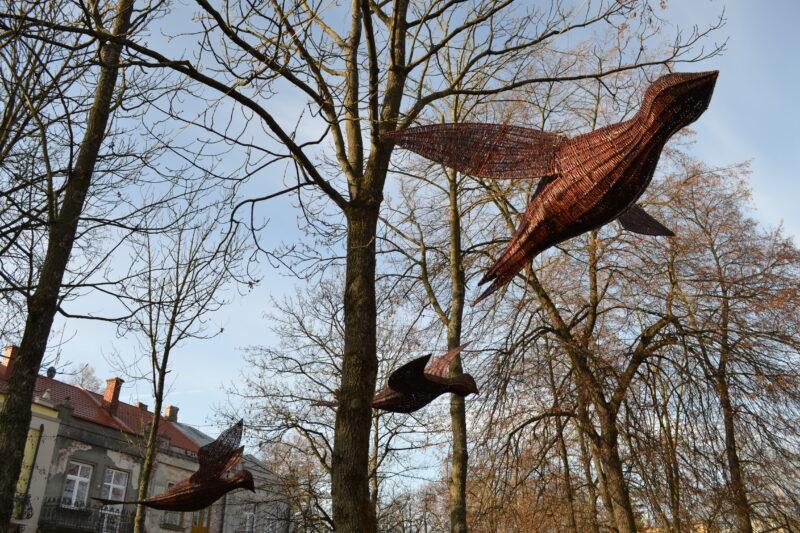 Trzy ptaki wykonane zwikliny zawieszone między drzewami