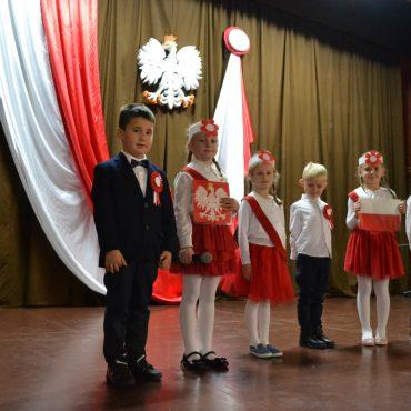 Odświętnie ubrane dzieci z biało-czerwonymi kotylionami stoja na scenie. Z tyłu sceny biało-czerwona flaga i biały orzeł z koroną