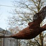 Duży wiklinowy ptak zawieszony między drzewami. Ztyłu budynki