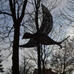 Duży wiklinowy ptak zawieszony między drzewami.
