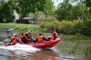 Pięciu strażaków wczarnych czapkach ipomarańczowych kamizelkach ratunkowych płynie czerowną łodzią zbuałym napisem Straż Pożarna
