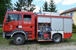 czerwono-srebrny samochód strażacki ustawiony bokiem, zotwartą częścia magazynowąz
