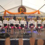 Grupa dziewcząt wbiałych bluzkach iczarnych spódniczkach zbiało-różowymi ozdobami tańczy nascenie.