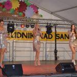 Trzy kobiety wsrebrnych sukienkach mini tańczą nascenie. Dwie śpiewają domikrofonu