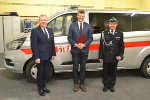Trzech mężczyzn - dwóch wgarniturach ikrawatach, atrzeci poprawej wuroczystym mundurze strażackim. Ztyłu srebrny samochód zczedrwonym paskiem wzdłuż karoserii