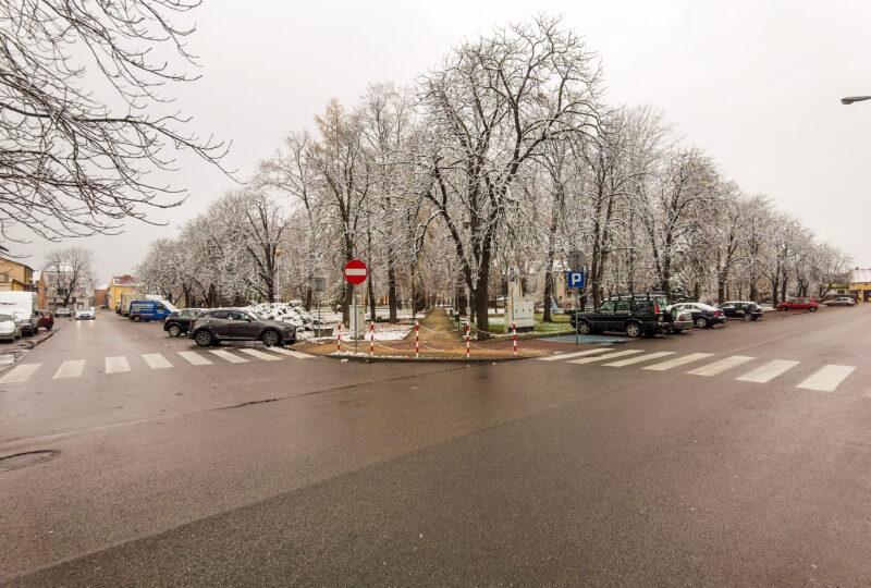 Dwie schodzace się ulice, przy nich zaporkowane samochody. Pomiędzy ulicami drzewa przyprószone śniegiem