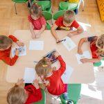 Dzieci ubrane wczerwone bluzki siedzą nazielonych krzesłach przy stołach irysują