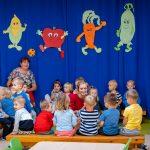 Grupa dzieci siedzi naławkach, wśród nich dwie kobiety. Wtle błekitna kotara zrysunkami spersyfikowanych warzyw