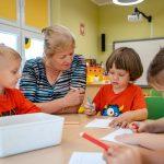 Kobieta zwłosami blond ubrana wbluzkę wczarne pasy siedzi ztrojgiem dzieci, które rysują