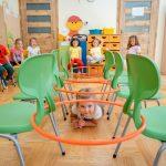 Dziewczynka wblond włosach czołga sie między zielonymi krzesłami. Wtle grupa dzieci