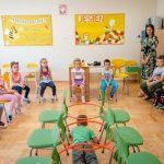 Chłopiec wzielonej bluzce czołga się między zielonymi krzesłami. Wtle siedzi grupa dzieci istoi kobieta wkolorowej sukni