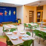 Stołówka dla dzieci składa sie zniskich jasnych stołów, aprzy nich zielone krzesła. Nastole talerze iszklanki znapojem