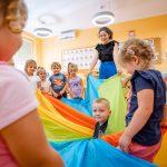 Grupa dzieci bawi się kolorowym suknem. Ztyłu kobieta wczarnej bluzce iniebieskich spodniach