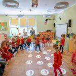 Dziewczynki wczerwonych bluzeczkach skaczą pokołach wyświetlających sią napodłodze. Obok siedzą dzieci nakrzesłach
