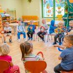 Dzieci siedzą woręgu naczerwonych krzeslach itrzymaja kolorowe kółka