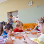 Trzy dziewczynki idwóch chłopców siedzą przy stole ijedzą zbiałych talerzy. Ba stołach widac szklanki znapojem