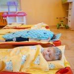 Chłopiec wblond włosach śpi przykryty żółta kołdrą wewzór wbiałe owieczki. Ztyłu nainnym łóżku lezy dziecko całe przykryte niebieską kołdrą