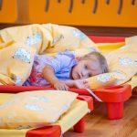 Dziewczynka zwłosami bląd leży wdziecięcym łóżeczku zżółto białą pościelą