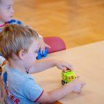 Dwóch chłopców wkoszulkach zkrótkim rękawkami bawi się nastole małymi pojazdami