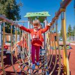 Dziewczynka wczerwonej bluzeczce irózowych rajstopach idzie pomoście linowym naplacu zabaw