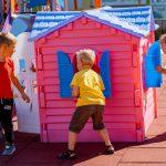 Trzech chłopców stoi naplacu zabaw wokół rózowego domku zplastiku