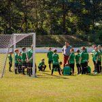 Chłopcy wzielono-czarnych strojach piłkarskich stoja namurawie obok bramki dopiłki noznej. Wśród piłkarzy mężczyna wbrązowych spodniach iszarej koszulce
