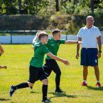 Chłopcy wzielono-czarnych strojach piłkarskichbiegną zwyciągnietymi doprzodu rękami. Ztyłu stoi mężczyna wgranatowych spodeńkach ibiałej koszulce