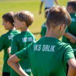 Chłopcy wzielonych koszulkach zbiałym napisem UKS Orlik stoja namurawie boiska