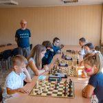 Ośmiu młodych szachistów siedzących naprzeciwko siebiegra wszachy. Ztyłu starszy mężczyzna wgranatowym t-shircie iokularach