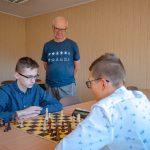 Dwóch chłopaków wniebieskich koszulach siedzi przy stole igra wszachy. Ztyłu starszy mężczyzna wgranatowym t-shircie iokularach