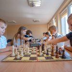 Młodzi szachiści - chłopiec wszarej bluzce polo idziewczynka wgranatowej bluzeczce grają wszachy