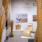 Meble iformy zwikliny ustawiony napostumentach wsali wystawowej. Naścianach kolorowe zdjęcia