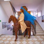 Rzeźba zwikliny - jeździec zniebieską flagą nakoniu. Rzeżba ustawiona naklatce schodowej