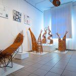 Oryginalne meble iformy zwikliny ustawiony napostumencie wsali wystawowej. Naścianie kolorowe zdjęcia
