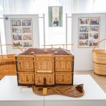 Ekspozycja wyrobów zwikliny - domku idwóch dużych koszyków. Ztyłu plansze zezdjęciami.