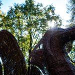 Rrzeźba smoka zciemnobrązowej wikliny ustawiona natle drzew