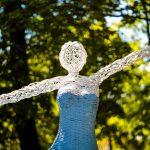 Rzeźba tancerki umieszczona wplenerze wykonana zwikliny pomalowanej nabiało iniebiesko