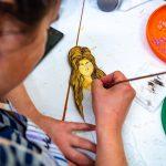 Kobieta wkolorowej bluzce maluje postać kobiecą. Nastole leżą dwa talerze = pomarańczowy izieloby służące dorozrabiania farb