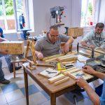 Czterech mężczyzn wroboczych ubraniach pracuje wwarsztacie stolarskim. wtle maszyny