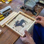 Reze mężczyzny oprawiają obrazek zrobiony technika wypalania nadrewnie. Obraze przedstawia łosia.