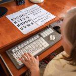 Kobieta siedzi przy klawiaturze iprzepisuje litery wydrukowane nadwóch kartkach
