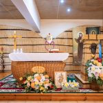 Ołtarz zwikliny przedołtarzem sztuczne kwiaty. Wgłębi dwa rollupy zpostaciami świętych, obrazek ikrzyż