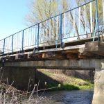 Most zbudowany zdrewnianych desek ikamienno-betonowych przęseł. Namoście biało-niebieska balustrada.