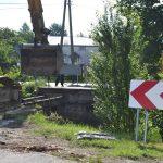 Koparka stoi przedzdemontowanym mostem. Napierwszym planie znak zakazu ztablica zczarnymi literami napomarańczowym tle