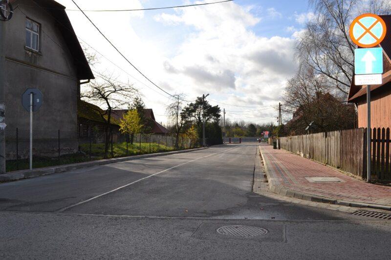 Przebudowana ulica znowym chodnikiem poprawej stronie, oraznową nawierzchnią asfaltową